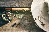 stock photo of fishing rod  - Fly fishing rod with canvas hat on wood - JPG