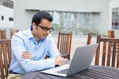 pic of indian blue  - Closeup portrait young man in blue shirt and black glasses listening to headphones browsing digital computer laptop isolated background of sunny outdoor gray building with brown chairs background - JPG