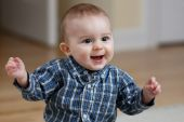 stock photo of brown-haired  - Caucasian baby boy dancing and smiling in flannel shirt - JPG