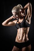stock photo of muscle builder  - Beautiful athletic woman showing muscles on dark background - JPG