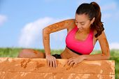 stock photo of mud  - Woman competing in a mud run race - JPG
