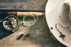 image of fly rod  - Fly fishing rod with canvas hat on wood - JPG