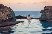 foto of silence  - real woman in  pool overlooking the sea  at sunset  in a moment of silence - JPG