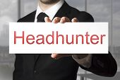 picture of soliciting  - businessman in black suit holding white sign headhunter - JPG