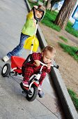 stock photo of tricycle  - toddler girl walking with baby sister on the tricycle - JPG
