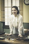 stock photo of 1950s  - 1950s smiling business woman leaning on office desk - JPG