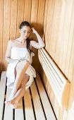 picture of sauna woman  - Young woman relaxing on a bench at the sauna - JPG