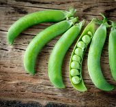 pic of pea  - Some colorful green pea pods on old wooden background - JPG
