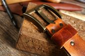 stock photo of leather tool  - Craft tools with leather belt on table close up - JPG