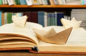 image of old boat  - Origami boats with old book on bookshelves background - JPG