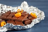 picture of orange peel  - Chocolate with orange peels in foil on wooden table - JPG