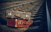 stock photo of old suitcase  - Two old suitcases lie on railway rails - JPG