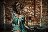 foto of bloody  - Horrible bloody zombie girl standing outdoor by the brick wall - JPG