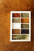 stock photo of bay leaf  - set of different spices (pepper, salt, turmeric, bay leaves, chili, herbs) in a wooden box - JPG