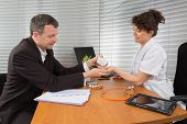 stock photo of prophylactic  - Businessman with Female Doctor at her office - JPG