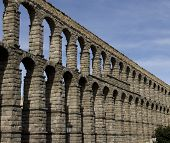 image of aqueduct  - Ancient Aqueducts in Segovia Spain against a blue sky background - JPG
