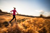 stock photo of fall day  - Young woman running outdoors on a lovely sunny winter - JPG