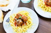 stock photo of cilantro  - Homemade Italian meatballs garnished with cilantro and parmesan cheese over spaghetti for dinner - JPG