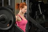 pic of squatting  - young red haired girl doing squats with barbell on smith machine - JPG