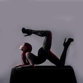 stock photo of plinth  - Acrobat girl on the plinth with red hair and heels - JPG