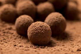 stock photo of desert christmas  - Close up of group of appetizing black chocolate truffles covered in cocoa dust - JPG