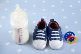 image of nipples  - Baby shoes with nipple and bottle of milk on blue background - JPG