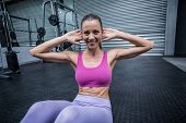 pic of crunch  - Portrait of a smiling woman doing abdominal crunch - JPG