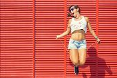 picture of jump rope  - Happy Woman jumping rope on red background - JPG