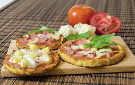 stock photo of crust  - Three small round baked pizzas made of cauliflower crust and topped with bacon ham halloumi cheese cottage cheese lountza pineapple turkey tomato sauce and basil on a wooden chopping board and bamboo tablecloth - JPG