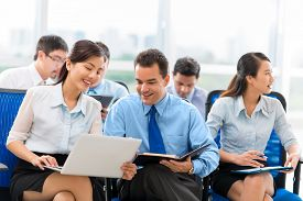 pic of seminar  - Young woman sharing some information on laptop with her colleague during the business seminar  - JPG