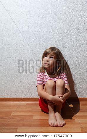 Постер, плакат: Маленькая девочка в одежда выглядит грустно в угол откуда приходит свет, холст на подрамнике