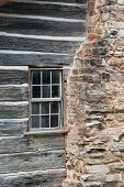 stock photo of log cabin  - The window and rock chimney of and old log cabin - JPG