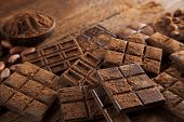Dark homemade chocolate bars and cocoa pod on wooden poster
