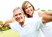 image of elderly couple  - Happy smiling elderly seniors couple in park - JPG