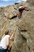 A female belaying a male on a steep rock face.  Shallow depth of field with the focus on the climbin