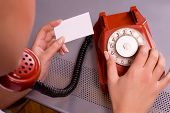 picture of dial pad  - Woman holding business card and dialing on red phone - JPG