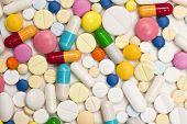 Постер, плакат: Ассорти цветные таблетки и капсулы на белом фоне