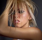 image of fluffing  - Passionate woman fluffing up blond hair - JPG