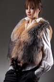 Fashion woman wearing fur jerkin over her white blouse