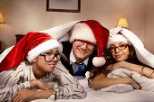 picture of promiscuous  - Manager with two his subordinates look out  cover in bed on New Year - JPG