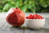 Ripe Pomegranate And Pomegranate Seeds In A White Bowl On A Rustic Table. Harvest Ripe Pomegranate . poster
