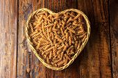 Integral Fusilli, Heart Bowl Over A Wooden Table, Top View. Wholemeal Pasta. poster