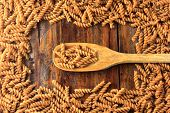 Top View Of The Whole Fusilli Pasta With Wooden Spoon, On A Wooden Background. poster