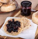 English Muffin Cut In Half And Spread With Blueberry Preserves On A Napkin With A Jar Of Preserves A poster