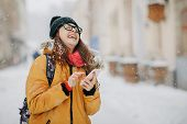 Portrait Of Teenage Girl Holding Mobile Phone Outside In Winter poster