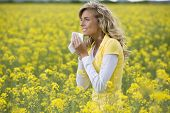 stock photo of hay fever  - Young woman sneezing in a flowers meadow - JPG