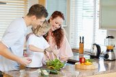 Couple letting their young child stir the salad
