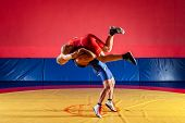 Two Greco-roman  Wrestlers In Red And Blue Uniform Wrestling  On Background On A Yellow Wrestling Ca poster