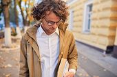 Handsome Young Man Wears Spectacles With Books Outdoors. College Male Student Carrying Books In Coll poster