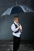 boy dressed in white shirt standing under umbrella in rain and smiles